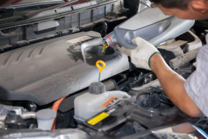 mechanic performing fluid flush in vehicle Lake Arbor Automotive & Truck Westminster Colorado