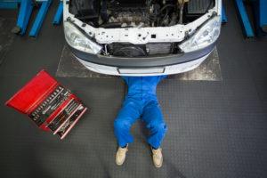 mechanic under car doing fuel pump repair Lake Arbor Automotive & Truck Westminster Colorado