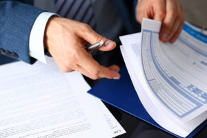 close up of man looking through Warranty paperwork Lake Arbor Automotive & Truck Westminster Colorado